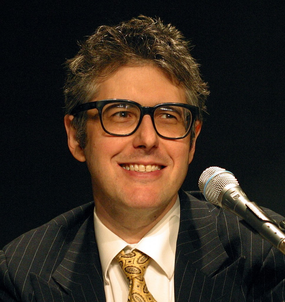A photo of Ira Glass smiling and looking into the distance. There is a microphone in front of him.