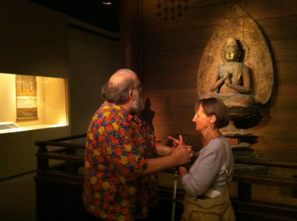 Dave and Linda are facing each other, standing a few feet in front of a Buddha statue. Dave is looking at the statue, and hoding Linta's arms. Linda is facing Dave and holding the pose.