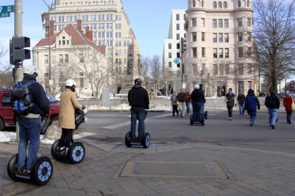 A group of five people riding motorized segway scooters riding single-file down the sidewalk curb cut and into the crosswalk. Washington DC in wintertime. They are wearing winter coats and helmets.